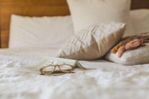 Blad og briller ligger på madras