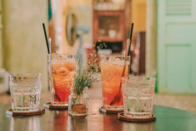 Flotte orange drinks med is og glas ved siden